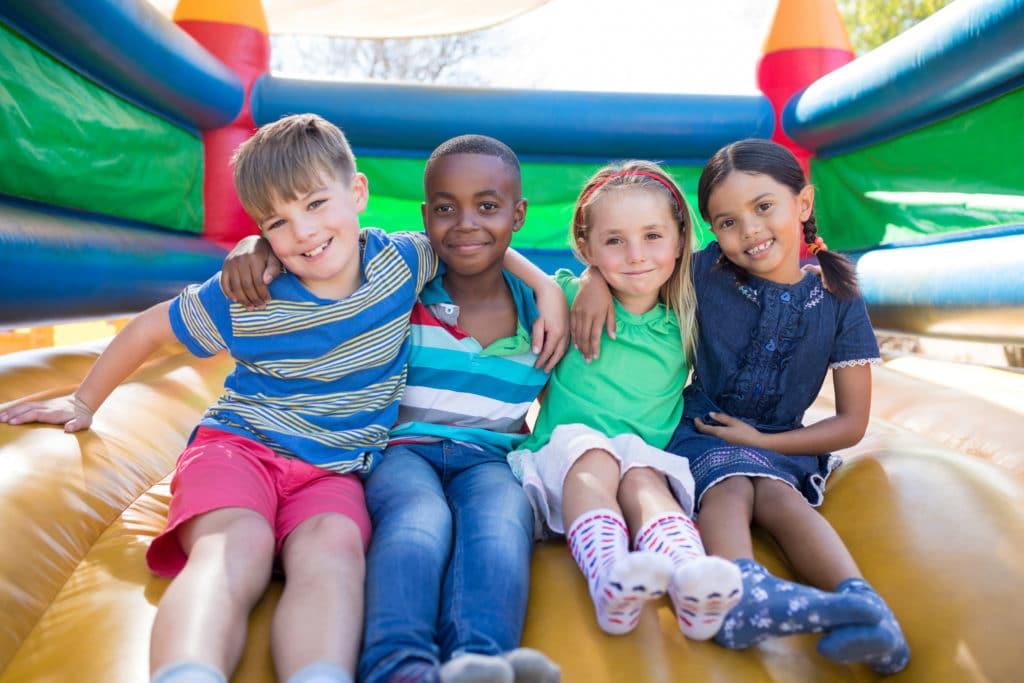 Kinder sitzen auf Hüpfburg