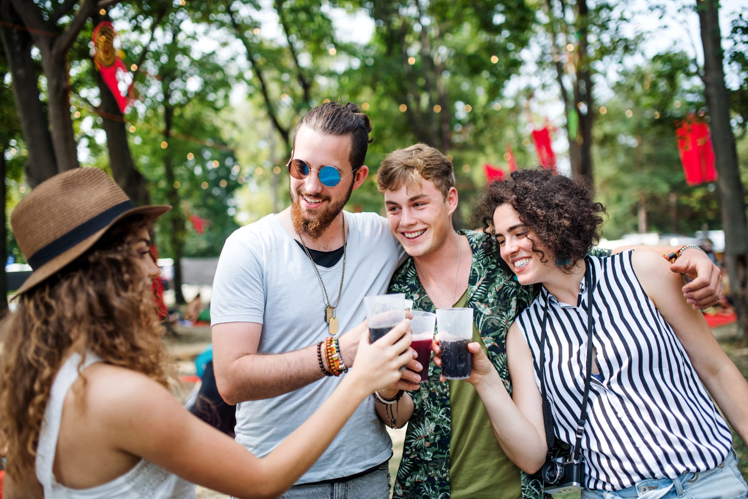 Group of young friends with drinks at summer festival, standing.