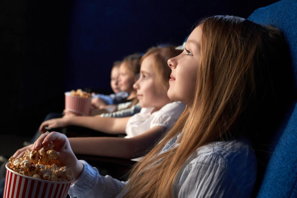 Kids sitting in comfortable chairs of movie theatre, watching attentively movie or cartoon. Beautiful girl holding popcorn bucket, enjoying film premiere.